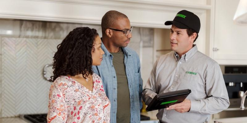 terminix exterminator talking to customers after a pest inspection